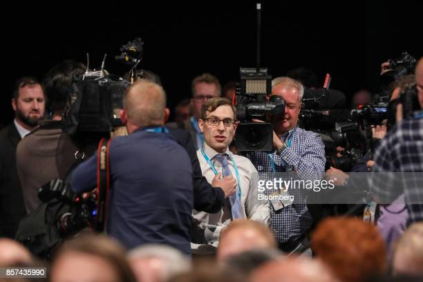Simon Brodkin comedian is escorted from the conference hall after handing Theresa May UK prime minister and leader of the Conservative Partya fake...
