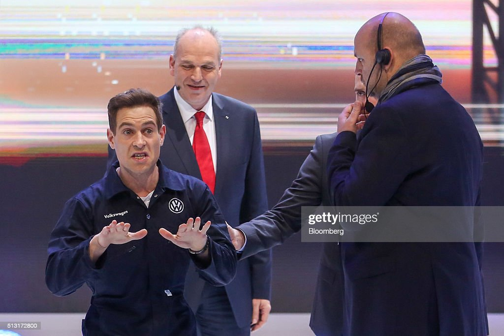 Simon Brodkin, comedian, left, gestures as he speaks while Juergen Stackman, sales chief of Volkswagen AG, center, looks on during a protest at a news conference on the first day of the 86th Geneva International Motor Show in Geneva, Switzerland on Tuesday, Mar. 1, 2016. The show opens to the public on Mar. 3, and will showcase the latest models from the world's top automakers. Photographer: Chris Ratcliffe/Bloomberg via Getty Images