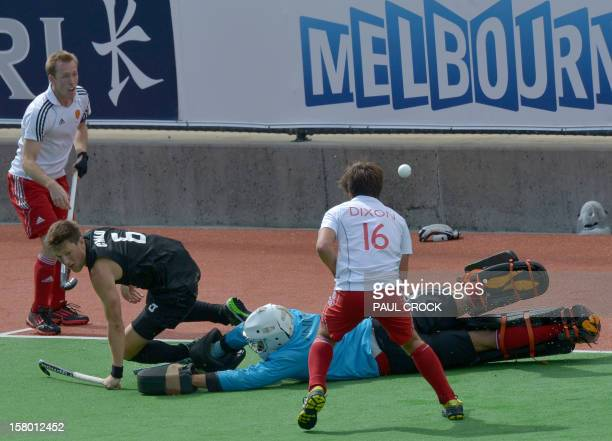 Simon Child of New Zealand gets the ball past keeper George Pinner of England during their match at the men's Hockey Champions Trophy tournament in...