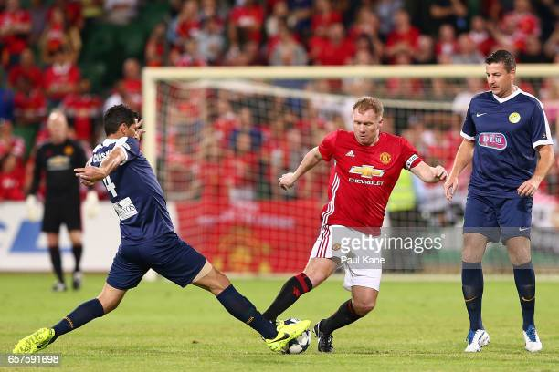 Simon Colosimo of the PFA Aussie Legends tackles Paul Scholes of the Manchester United Legends during the Manchester United Legends and the PFA...