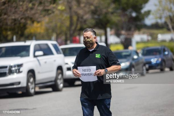 Simon Cooper offers prayers to people who attended an on line Sunday Service inside their cars at the Christian '412 Church Murrieta' parking lot on...