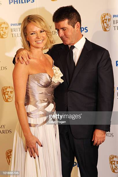 Simon Cowell and Amanda Holden pose in front of the winners boards at The Philips British Academy Television Awards held at The Palladium on June 6...