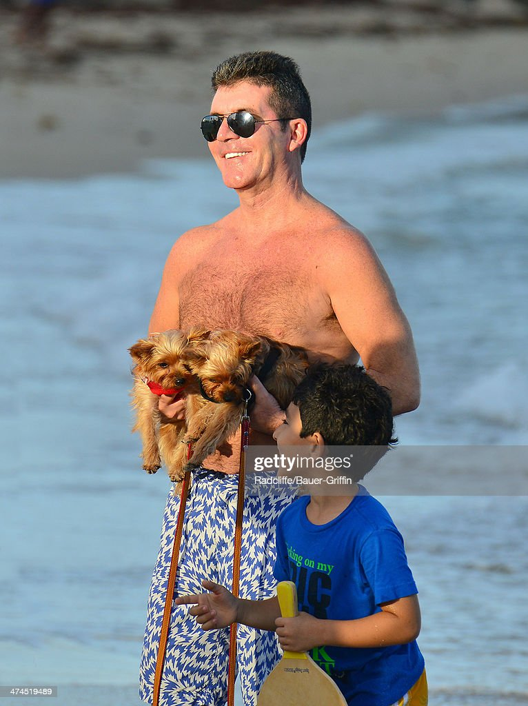 Simon Cowell is seen posing with a fan while walking his dogs at the beach on February 23, 2014 in Miami, Florida.