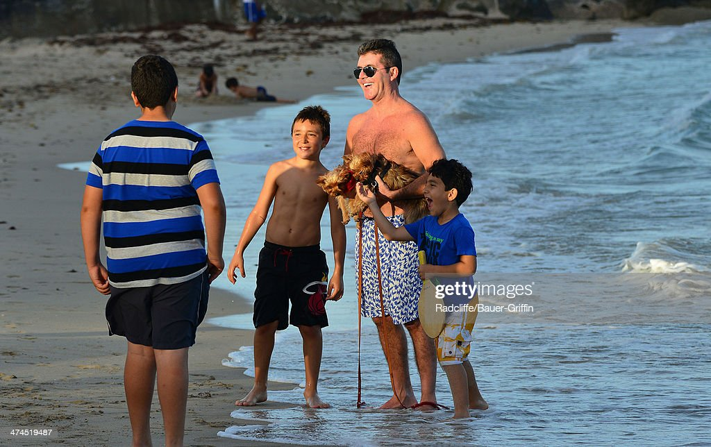 Simon Cowell is seen posing with fans while walking his dogs at the beach on February 23, 2014 in Miami, Florida.