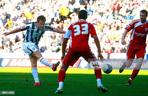 Simon Cox of West Bromwich Albion scores the opening goal past Kyle Naughton of Middlesbrough during the Coca Cola Championship match between West...