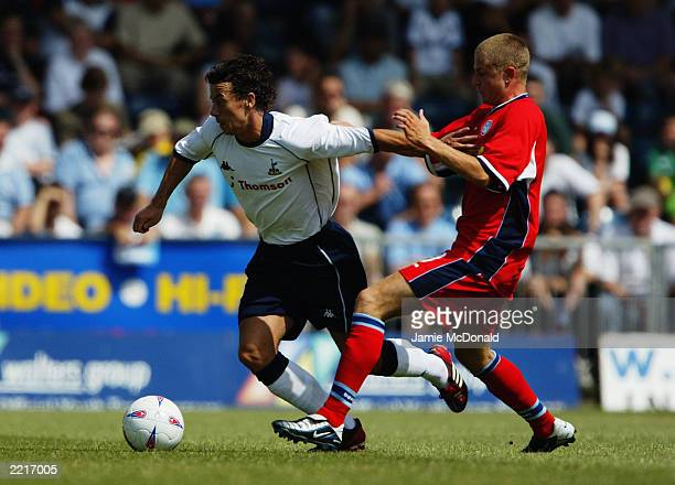 Simon Davies of Tottenham Hotspur takes the ball past Charlie Mapes of Wycombe Wanderers during the David Jones testimonial match held on July 19...