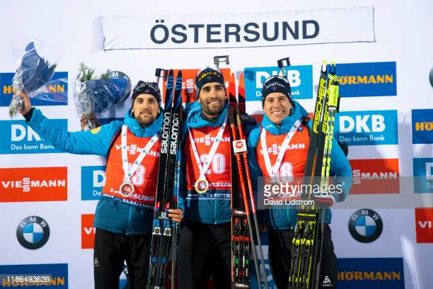 Simon Desthieux of France, Martin Fourcade of France and Quentin Fillion Maillet of France reacts during the prize ceremony during the Mens 20 km...
