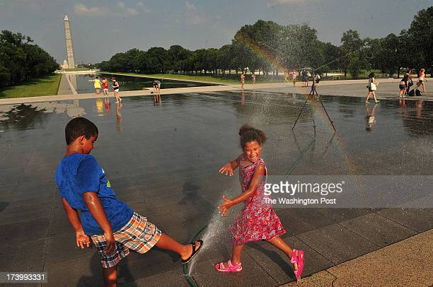 Simon Dixon left and his sister Annie Dixon of Magalia CA cool off from high temperatures and high humidity in a spray of water near the Lincoln...