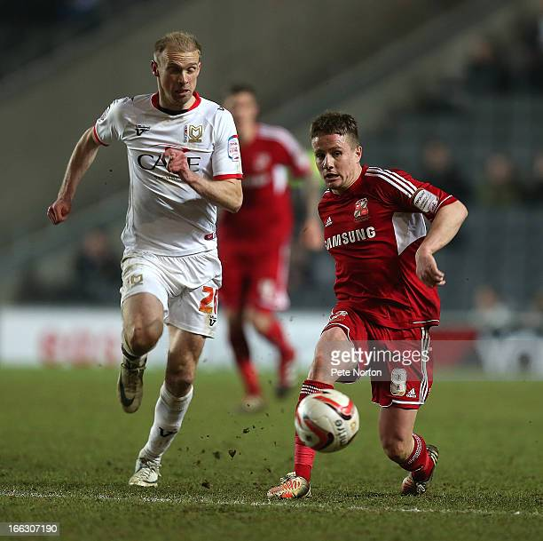 Simon Ferry of Swindon Town plays the ball watched by Luke Chadwick of MK Dons during the npower League One match between MK Dons and Swindon Town at...