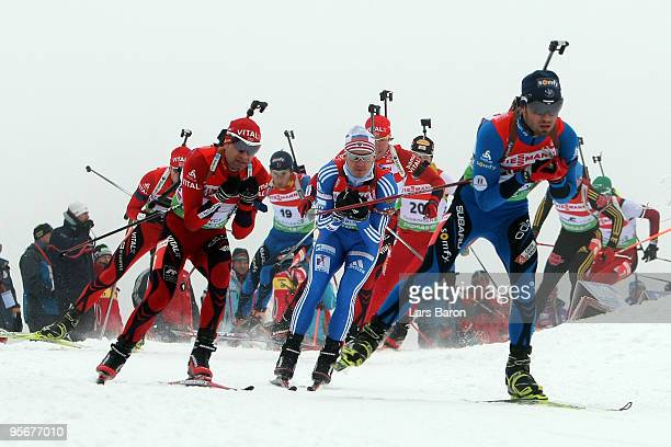 Simon Fourcade of France leads the pack into the first corner next to Ole Einar Bjoerndalen of Norway during the Men's 15 km mass start in the eon...