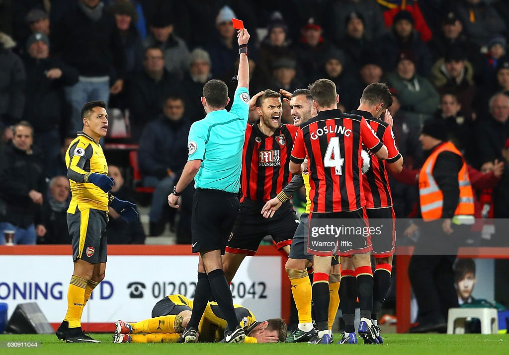 Simon Francis (4th R) of AFC Bournemouth reacts after receiving a red card by referee Michael Oliver (2nd L) after tackling on Aaron Ramsey of Arsenal during the Premier League match between AFC Bournemouth and Arsenal at Vitality Stadium on January 3, 2017 in Bournemouth, England.
