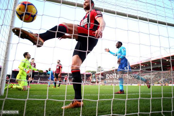 Simon Francis of AFC Bournemouth reacts as Danny Welbeck of Arsenal celebrates the first Arsenal goal scored by Hector Bellerin during the Premier...