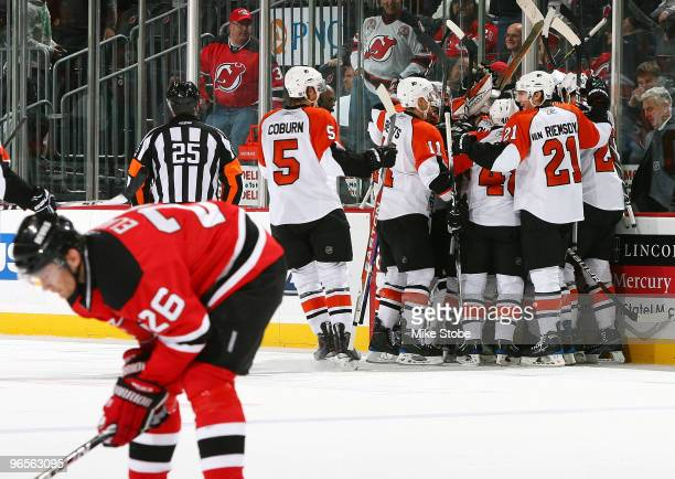 Simon Gagne of the Philadelphia Flyers is mobbed by his teammates after scoring the gamewinning goal in overtime as Patrik Elias of the New Jersey...