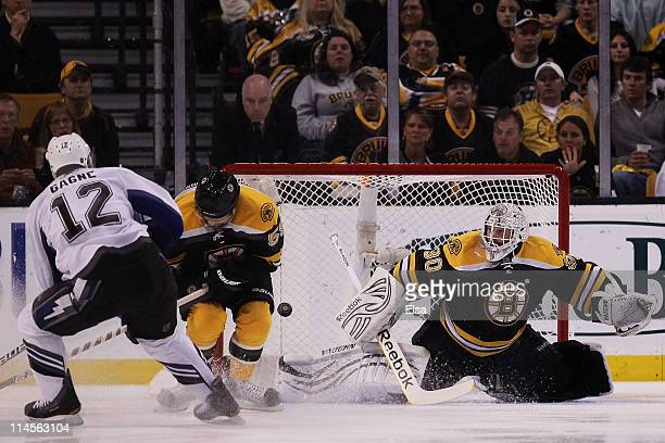 Simon Gagne of the Tampa Bay Lightning scores a first period goal past Johnny Boychuk and Tim Thomas of the Boston Bruins in Game Five of the Eastern...