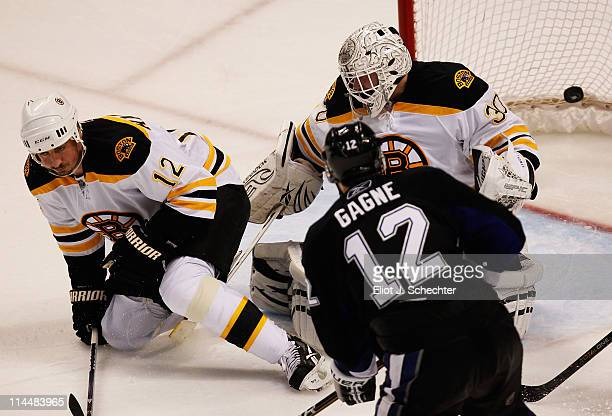 Simon Gagne of the Tampa Bay Lightning scores a third period goal past Tomas Kaberle and Tim Thomas of the Boston Bruins in Game Four of the Eastern...