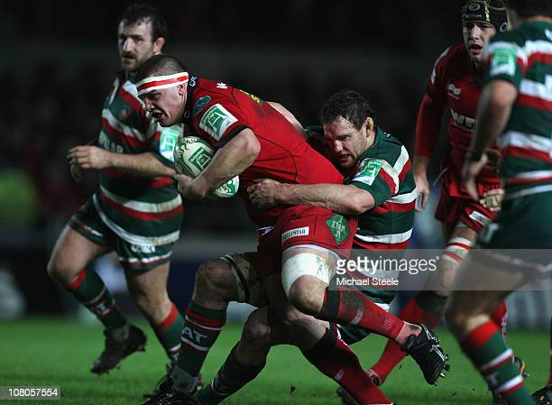Simon Gardiner of Scarlets is held up by Craig Newby during the Heineken Cup Pool Five match between Scarlets and Leicester Tigers at the Parc y...