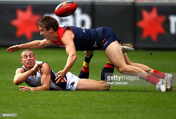 Simon Goodwin of the Crows handballs clear of Jack Trengrove of the Demons during the round three AFL match between the Melbourne Demons and the...