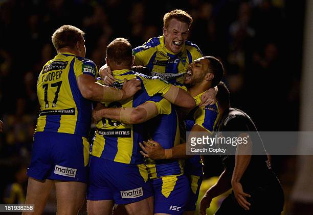Simon Grix of Warrington is mobbed by teammates after scoring his try durng the Super League Qualifying Semi Final between Warrington Wolves and...