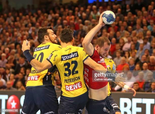 Simon Hald of SG FlensburgHandewitt is challenged by Gedeon Guardiola and Alexander Petersson of RheinNeckar Loewen during the DKB HBL Bundesliga...