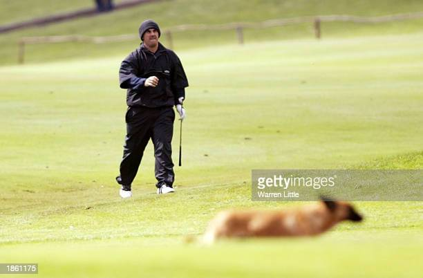 Simon Hurd of England walks down the first fairway as a dog crosses during the second round of the Madeira Island Open held at the Santo da Serra...