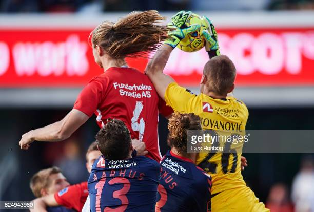 Simon Jakobsen of Silkeborg IF and Goalkeeper Aleksandar Jovanovic of AGF Aarhus compete for the ball during the Danish Alka Superliga match between...