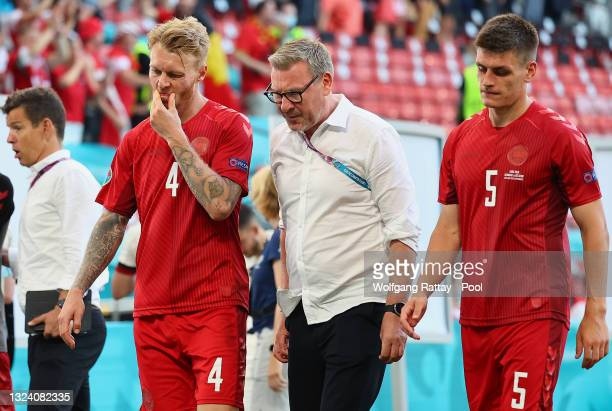 Simon Kjaer and Joakim Maehle of Denmark look dejected as they walk off the pitch with Kasper Hjulmand , Head Coach of Denmark following defeat in...