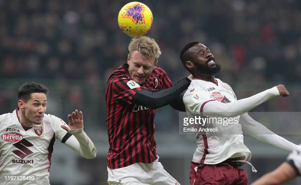 Simon Kjaer of AC Milan jumps for the ball aganist Nicolas Nkoulou of Torino FC during the Coppa Italia Quarter Final match between AC Milan and...