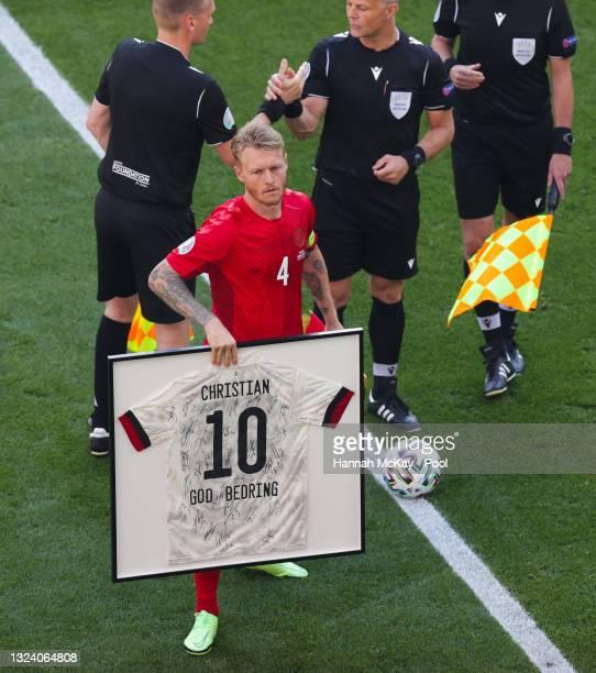 Simon Kjaer of Denmark holds a framed shirt of Christian Eriksen of Denmark prior to the UEFA Euro 2020 Championship Group B match between Denmark...
