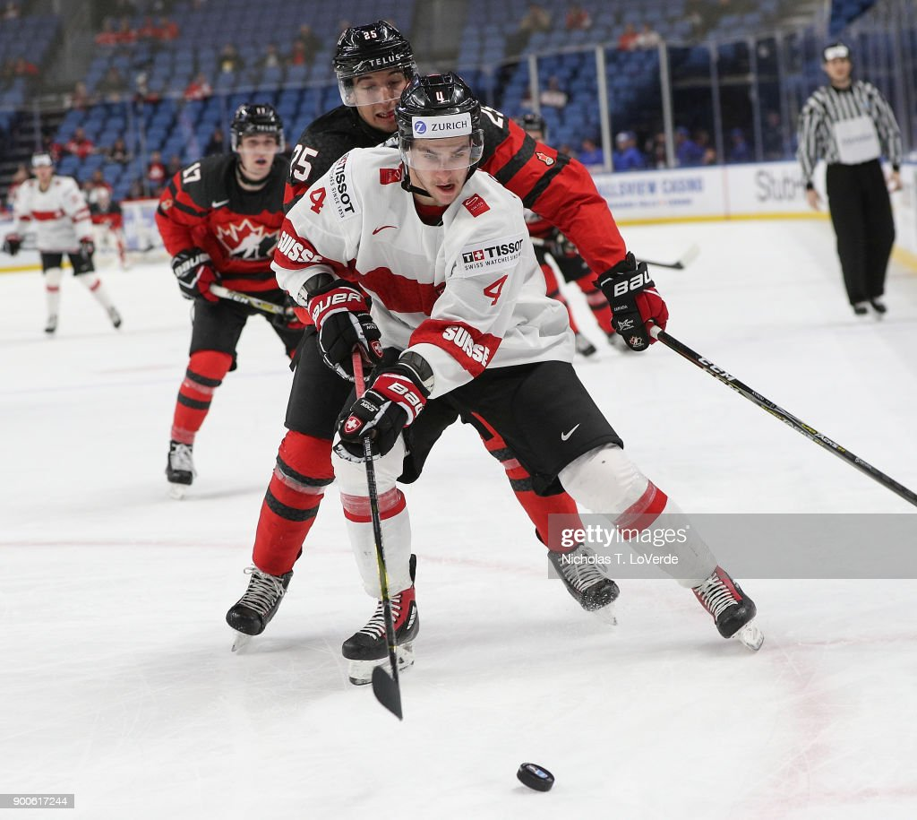 Simon le Coultre #4 of Switzerland skates for a loose puck with Jordan Kyrou #25 of Canada applying pressure during the third period of play in the Quarterfinal IIHF World Junior Championship game at the KeyBank Center on January 2, 2018 in Buffalo, New York.