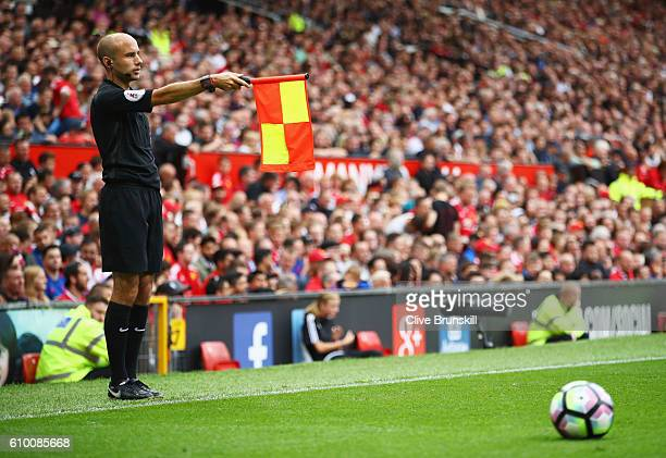 Simon long holds up the offside flag during the Premier League match between Manchester United and Leicester City at Old Trafford on September 24...