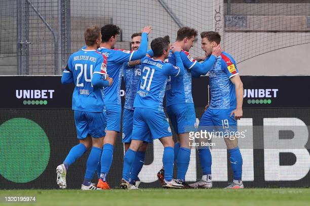 Simon Lorenz of Kiel celebrates his team's first goal with teammates during the Bundesliga playoff first leg match between 1. FC Koeln and Holstein...