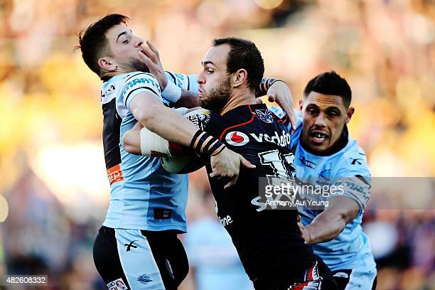 Simon Mannering of the Warriors fends against Jack Bird and Anthony Tupou of the Sharks during the round 21 NRL match between the New Zealand...