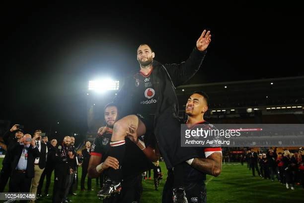 Simon Mannering of the Warriors is lifted up by his teammates David Fusitu'a and Ken Maumalo as he comes off the field after winning in his 300th...