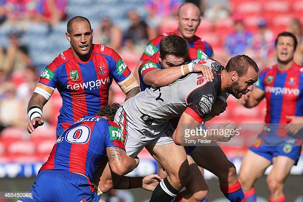 Simon Mannering of the Warriors is tackled by the Knights defence during the round one NRL match between the Newcastle Knights and the New Zealand...