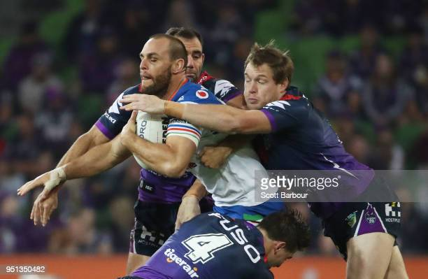 Simon Mannering of the Warriors is tackled by Tim Glasby of the Melbourne Storm and Cameron Smith of the Melbourne Storm during the round eight NRL...