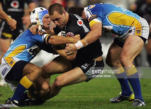 Simon Mannering of the Warriors is tackled during the round 16 NRL match between the Gold Coast Titans and the Warriors at Carrara Stadium on June...