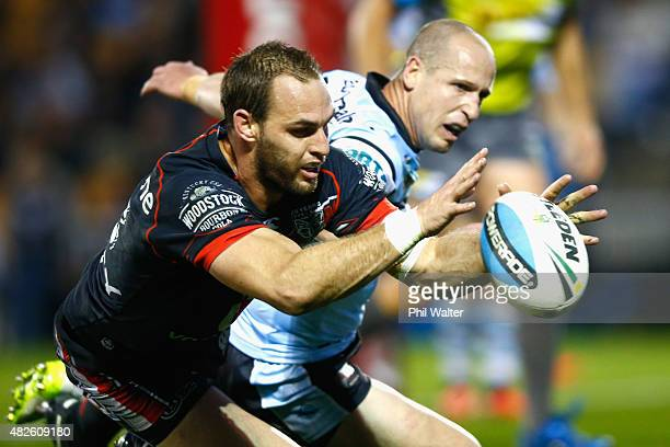 Simon Mannering of the Warriors scores a try under pressure from Jeff Robson of the Sharks during the round 21 NRL match between the New Zealand...