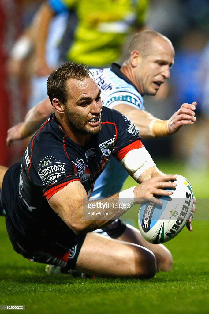 Simon Mannering of the Warriors scores a try under pressure from Jeff Robson of the Sharks during the round 21 NRL match between the New Zealand Warriors and the Cronulla Sharks at Mt Smart Stadium on August 1, 2015 in Auckland, New Zealand.