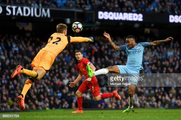 Simon Mignolet of Liverpool attempts to punch the ball as Raheem Sterling of Manchester City attempts to score during the Premier League match...