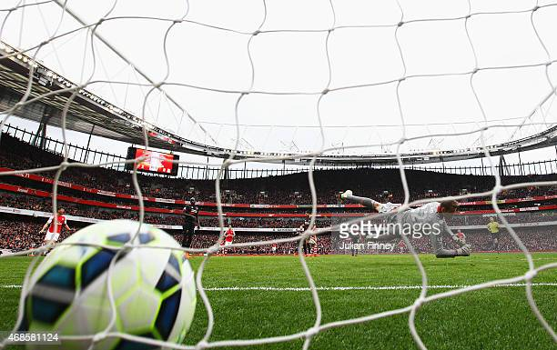 Simon Mignolet of Liverpool dives in vain as Alexis Sanchez of Arsenal scores their third goal during the Barclays Premier League match between...