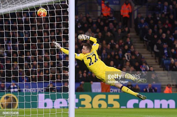 Simon Mignolet of Liverpool dives in vain as Jamie Vardy of Leicester City scores his team's first goal during the Barclays Premier League match...