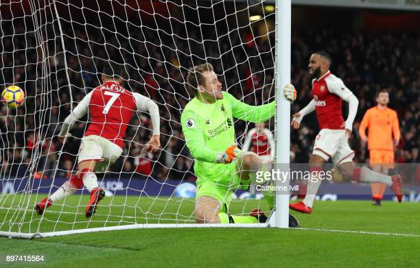 Simon Mignolet of Liverpool hangs onto the goal post after Alexis Sanchez of Arsenal scores a goal during the Premier League match between Arsenal...