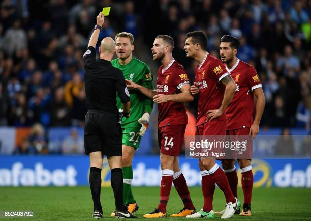 Simon Mignolet of Liverpool is shown a yellow card by referee Anthony Taylor during the Premier League match between Leicester City and Liverpool at...