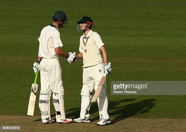 Simon Milenko of Tasmania is congratulated by Beau Webster of Tasmania after reaching his half century during day three of the Sheffield Shield match...