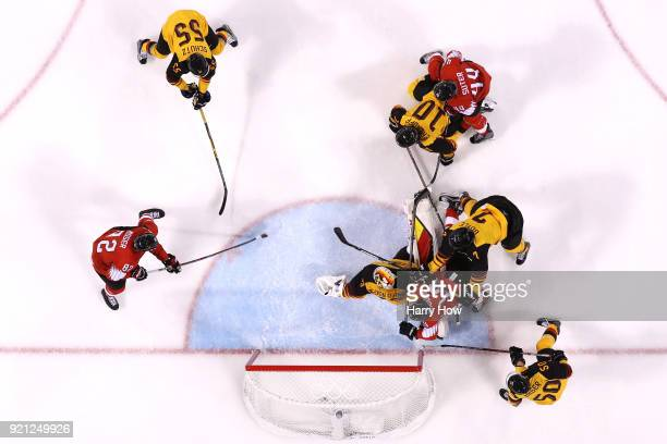 Simon Moser of Switzerland shoots and scores against Danny Aus Den Birken of Germany in the second period during the Men's Ice Hockey Qualification...
