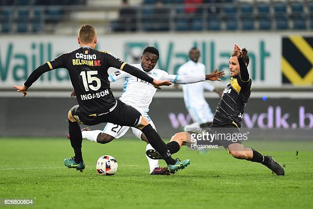 Simon Moses forward of KAA Gent is being tackled by Ingi Sverrir Ingason of sporting lokeren and Giorgos Galitsios of sporting lokeren during the...