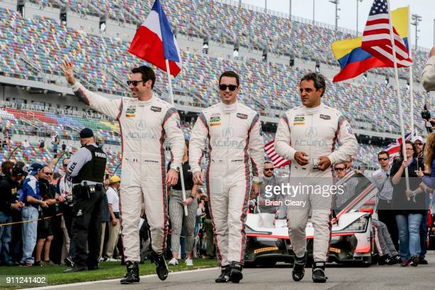 Simon Pagenaud L of France Dane Cameron C and Juan Pablo Montoya walk on the grid before the start of the Rolex 24 at Daytona at Daytona...