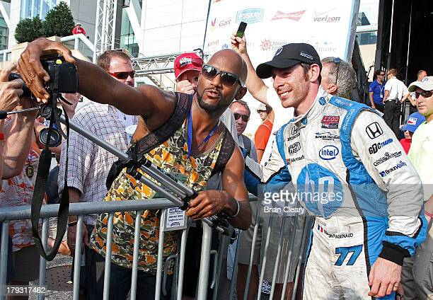 Simon Pagenaud of France driver of the Schmidt Hamilton Motorsports Honda Dallara poses for a photo with a fan in victory lane after winning the...