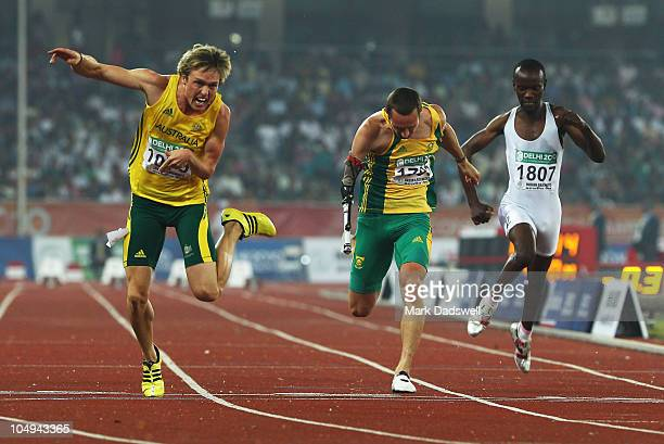 Simon Patmore of Australia crosses the line to win gold in the men's T46 100 metres final next to David Roos of South Africa and Herman Muvunyi of...