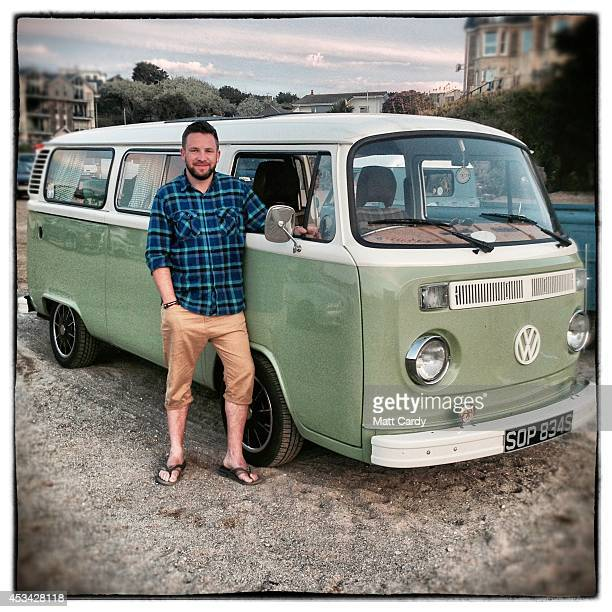 Simon Peacock from Stoke on Trent poses for a photograph besides his 1977 second generation or T2 bay window Volkswagen Transporter van in Newquay on...